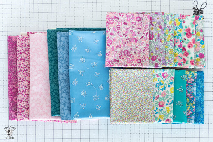 various bright colors of flat folds of liberty fabrics on white cutting mat