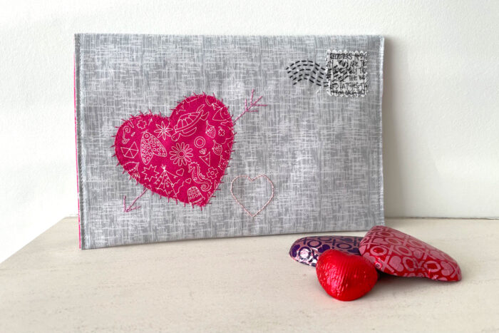 gray fabric envelope on white table with chocolates