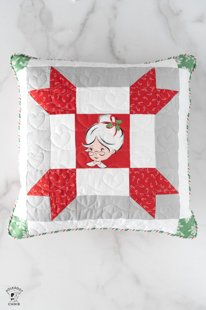 red, green and white patchwork christmas pillows on white tabletop