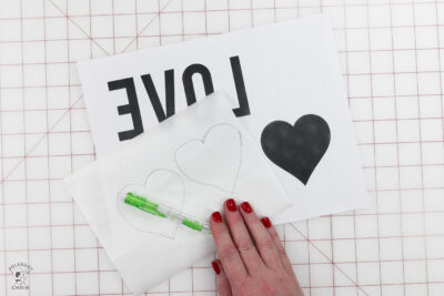 paper and templates on white cutting mat with hand and pencil