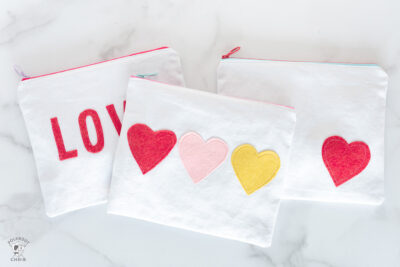 white canvas zip pouches with red lettering and hearts on white tabletop