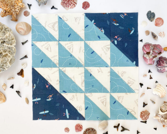 blue quilt block on white table with seashells around the perimeter