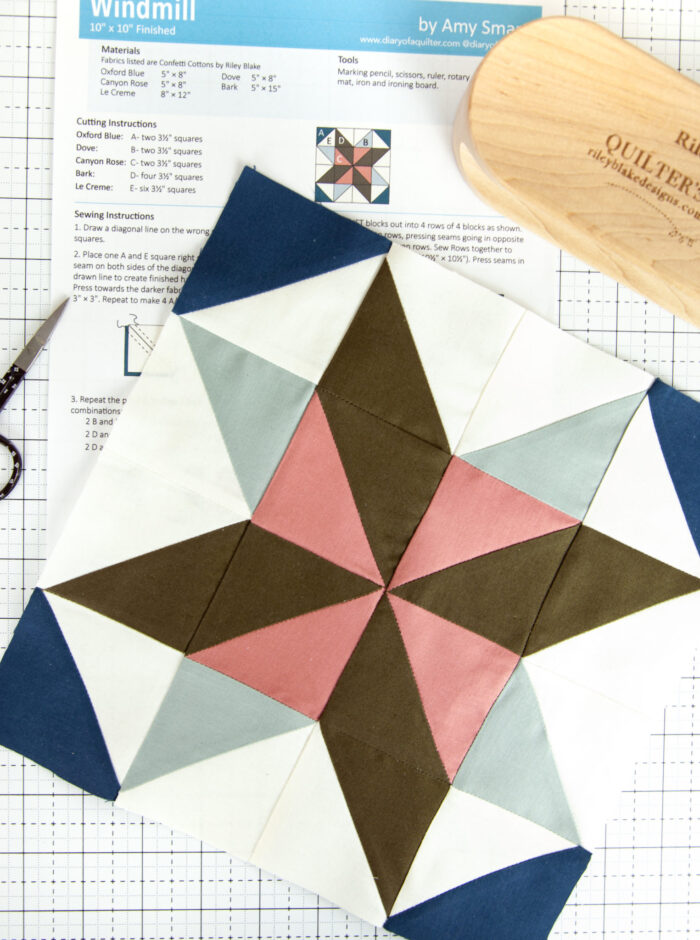 pink, brown and blue quilt block with papers on a white cutting mat