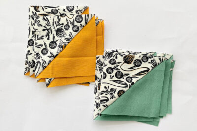 green white and yellow half square fabric triangles on white table