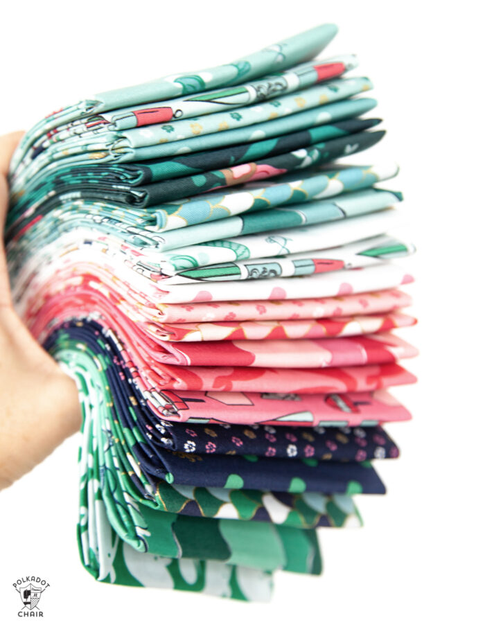 hand holding stack of colorful folded fabrics
