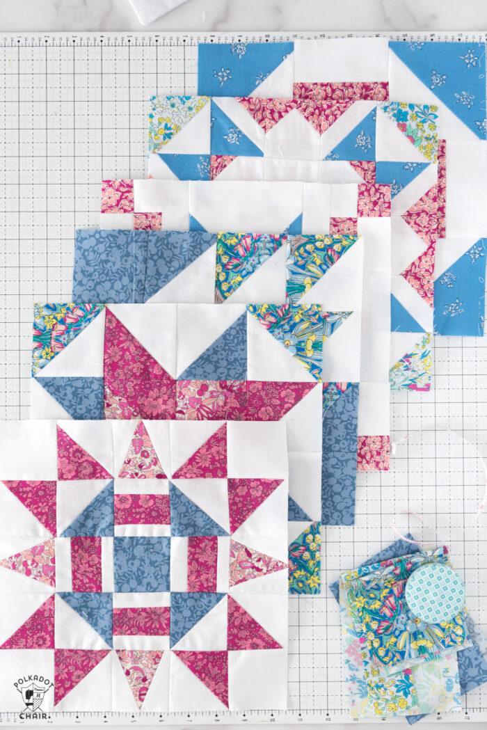 multiple red pink and white quilt block on white cutting mat