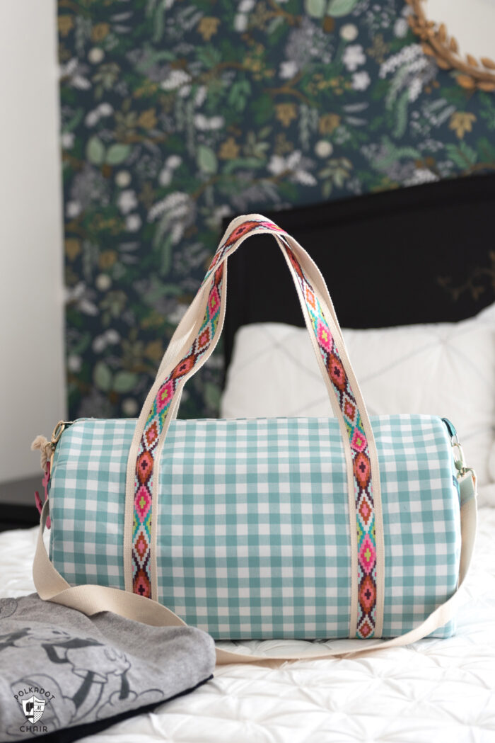 duffle bag on bed with white quilt and black headboard