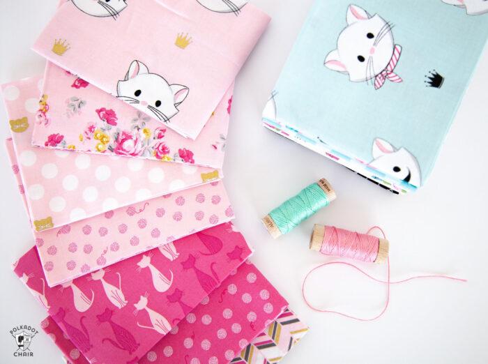 pink and aqua fabrics on white tabletop