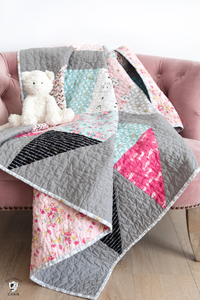 pink white and gray baby quilt on pink chair