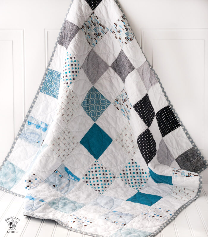 blue white and gray baby quilt on door
