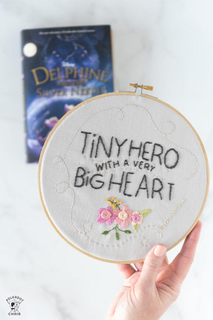 hand holding embroidery hoop with text