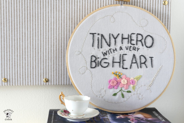 embroidery hoop on book with teacup leaning against pin board