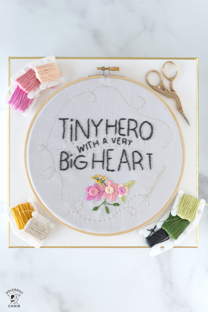embroidery hoop on box with thread and scissors