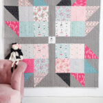 Pink, blue, gray & black baby quilt hanging on wall with pink chair and stuffed animals