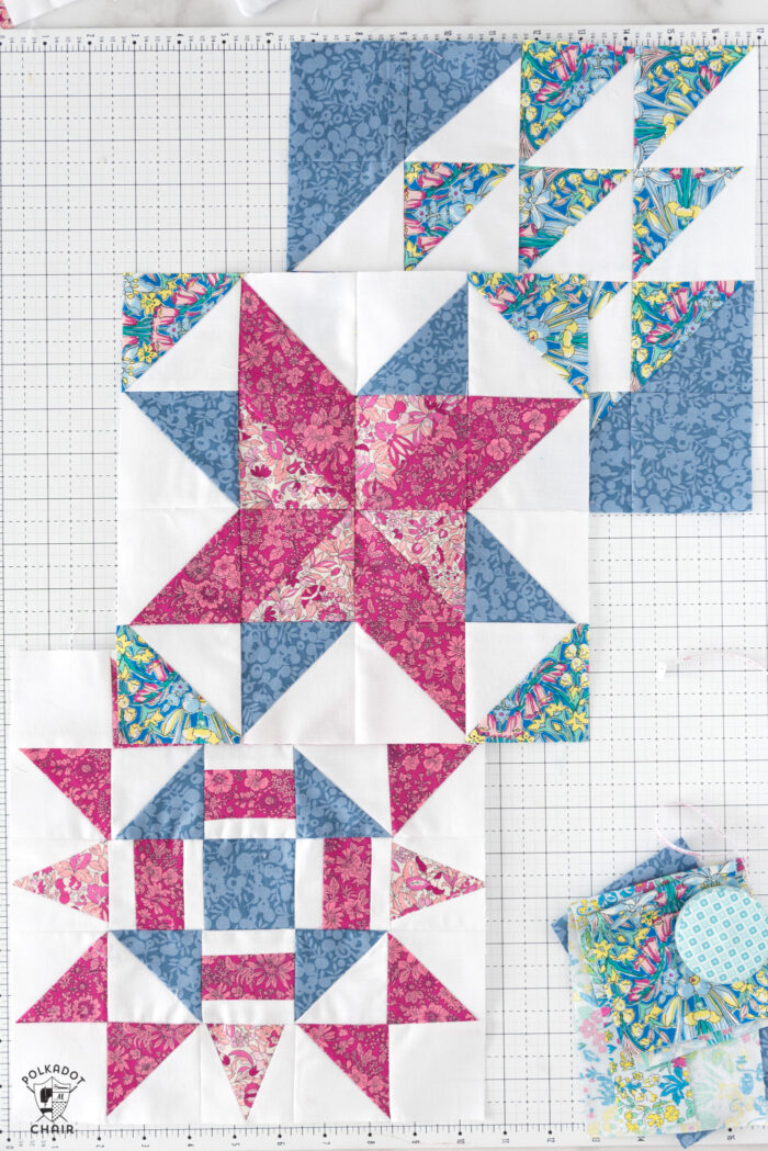 multiple red pink and white quilt blocks on white cutting mat