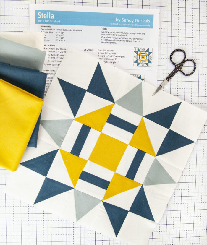 blue and yellow quilt block on white cutting mat