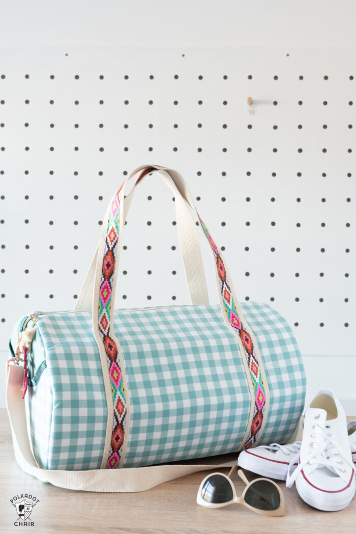 duffle bag in blue check in front of white peg wall