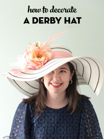 girl in white derby hat with pink flowers wearing a navy dress
