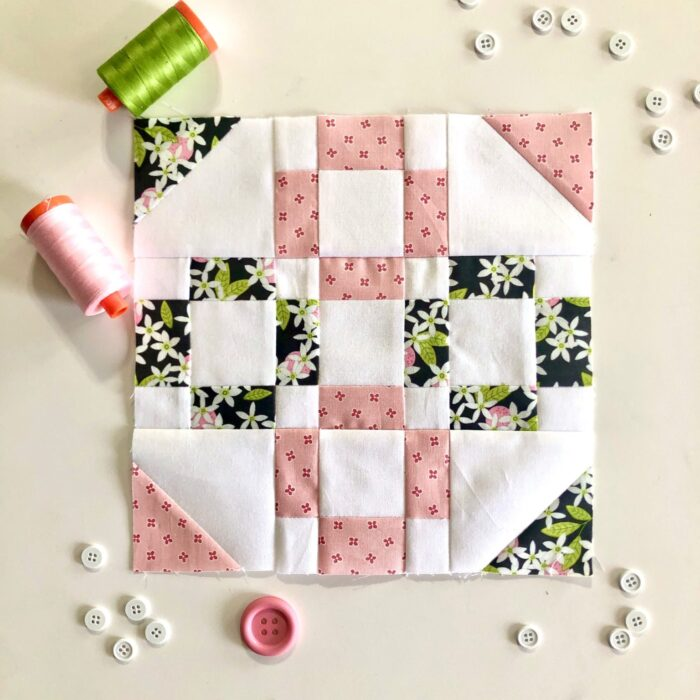 pink and green quilt block on table surrounded by sewing notions