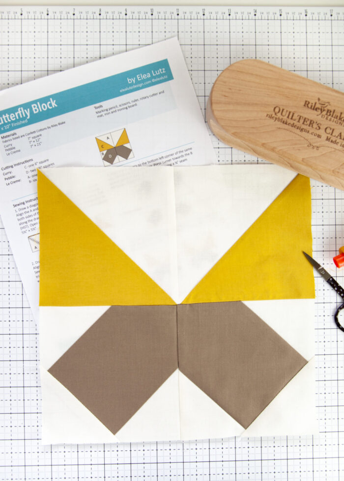 mustard yellow and taupe quilt block on white cutting mat
