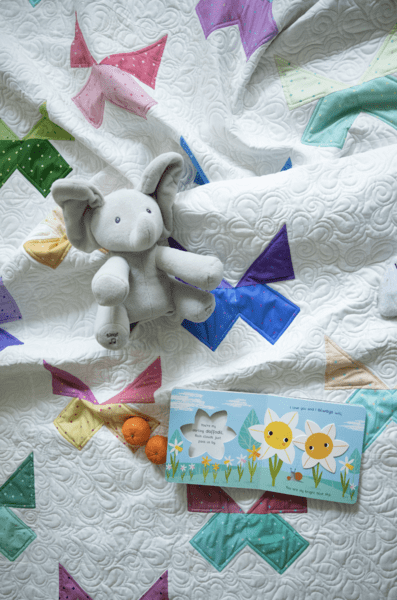stuffed animal on white quilt with colorful butterfly blocks