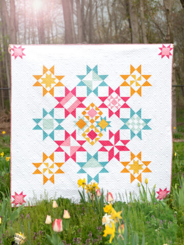 pink, blue and yellow geometric quilt in field of flowers