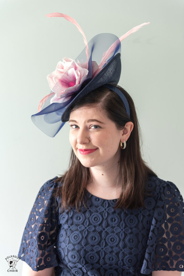 girl in navy dress wearing navy fascinator with pink flowers