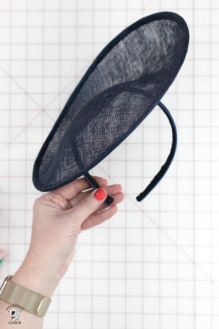 navy fascinator being held over white cutting mat
