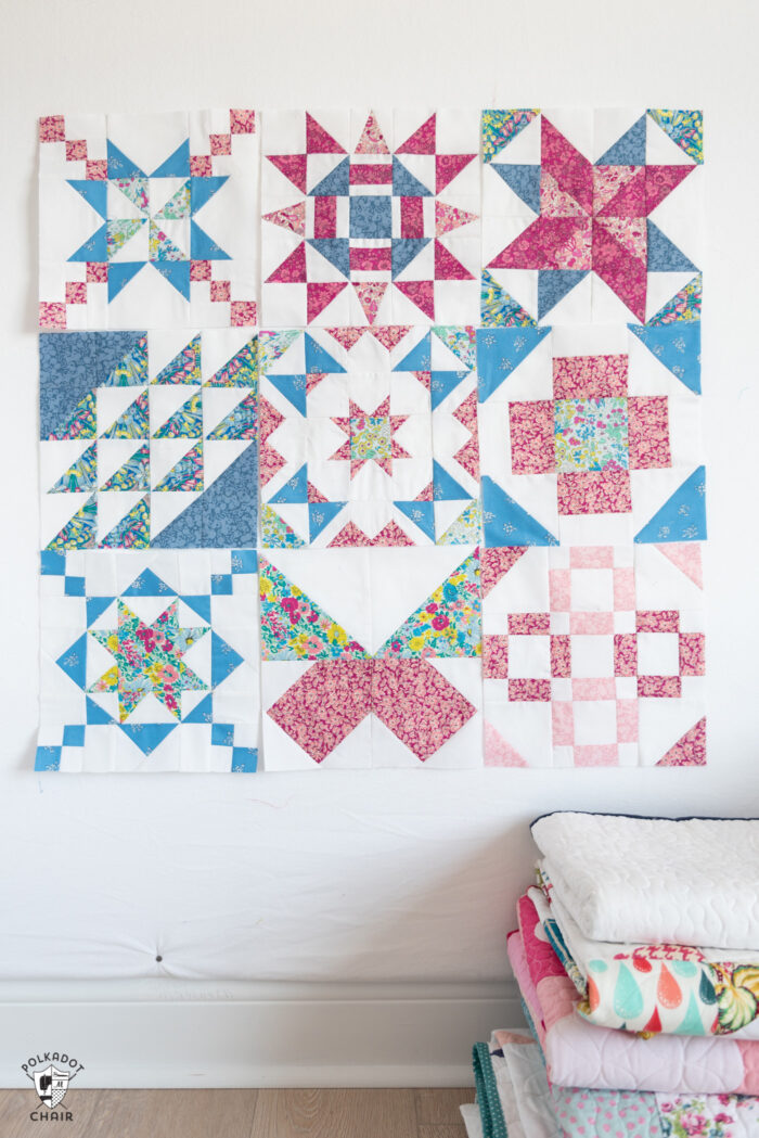 pink, blue and white sampler quilt blocks hanging on a design wall