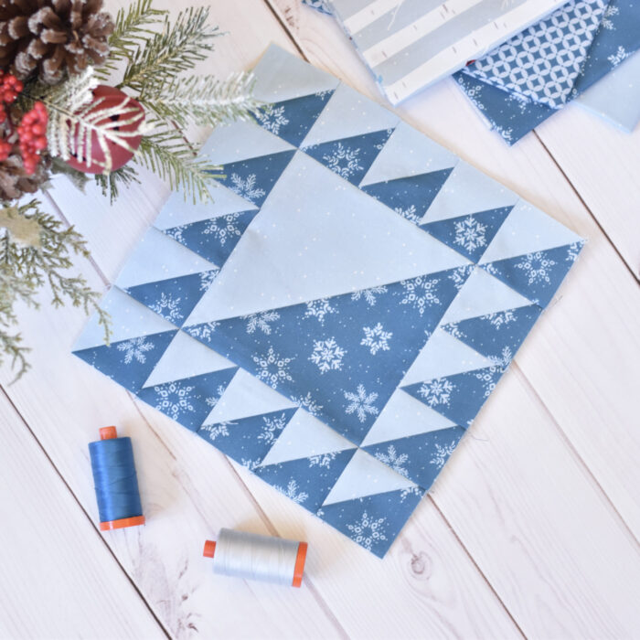 navy and white quilt block on cutting mat with quilting supplies