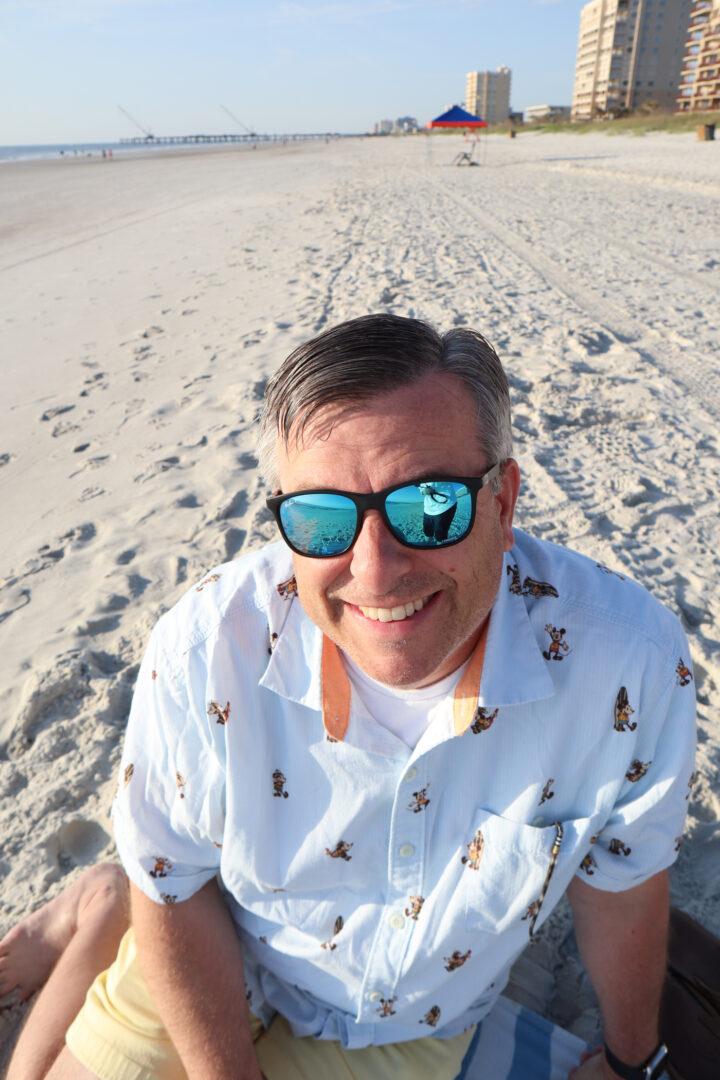 man sitting on beach wearing sunglasses