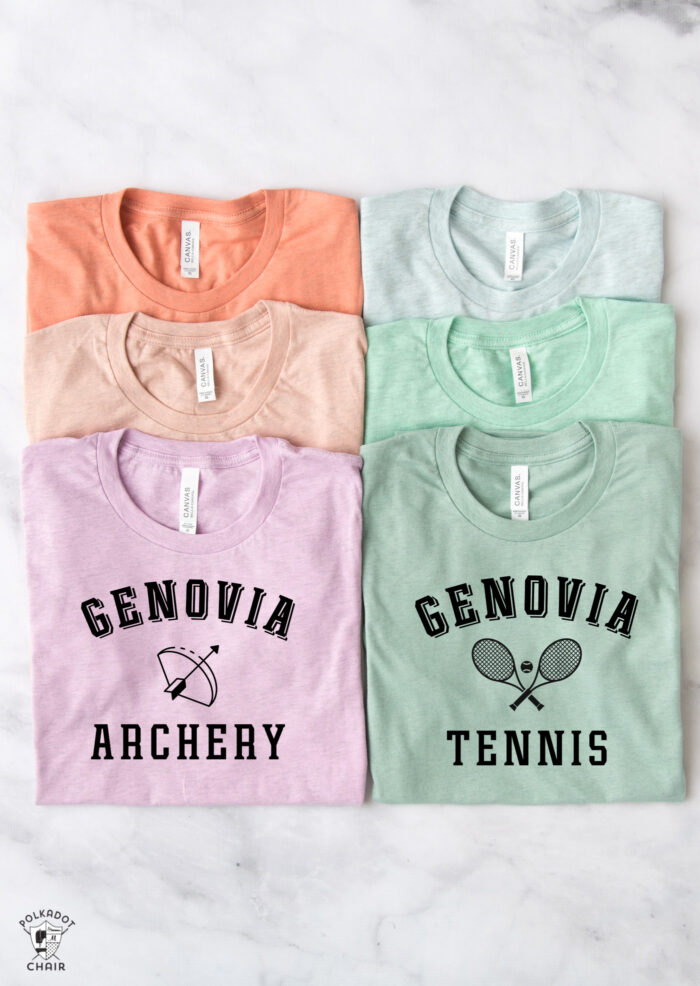 pastel colored t-shirts on white table with black lettrering