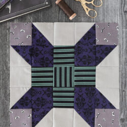 gray and green quilt block on gray table with sewing notions
