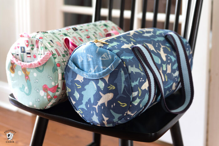 two duffle bags in aqua and blue sitting on chair in front of french doors