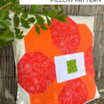 photo of orange and cream quilted pillow outdoors