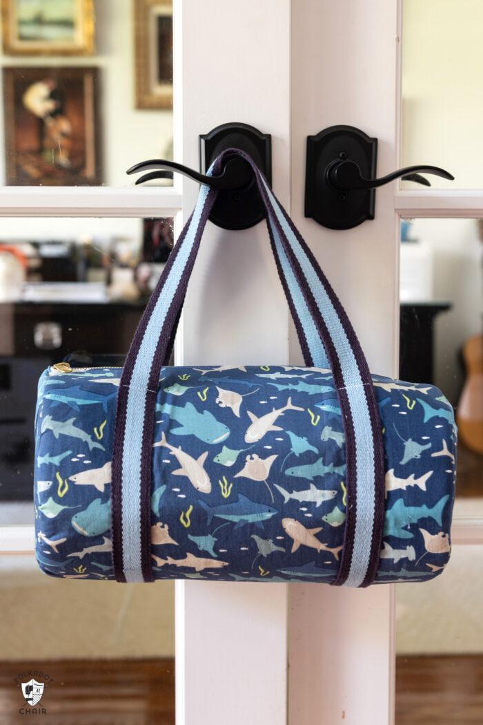 Blue duffle bag hanging on door handle