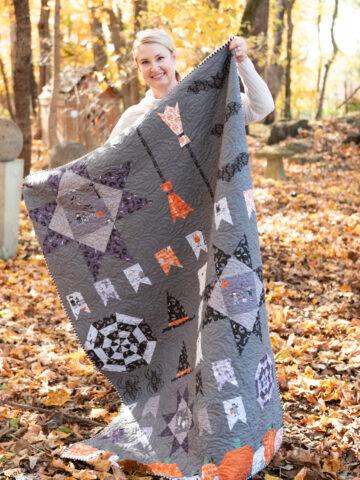 woman holding halloween quilt outdoors