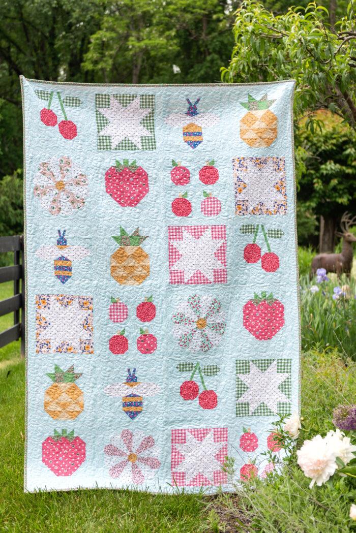 quilt hanging in front of garden