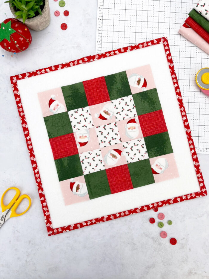 pink, red and green quilt block on white cutting mat