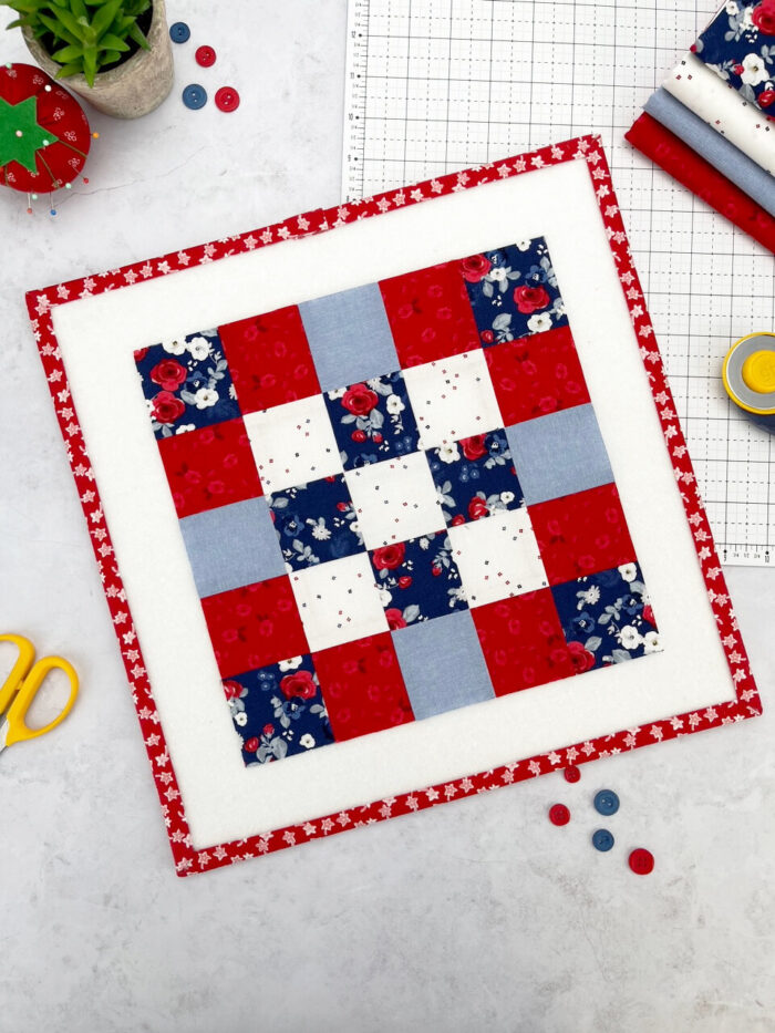 red white and blue quilt block on white cutting mat with buttons and scissors