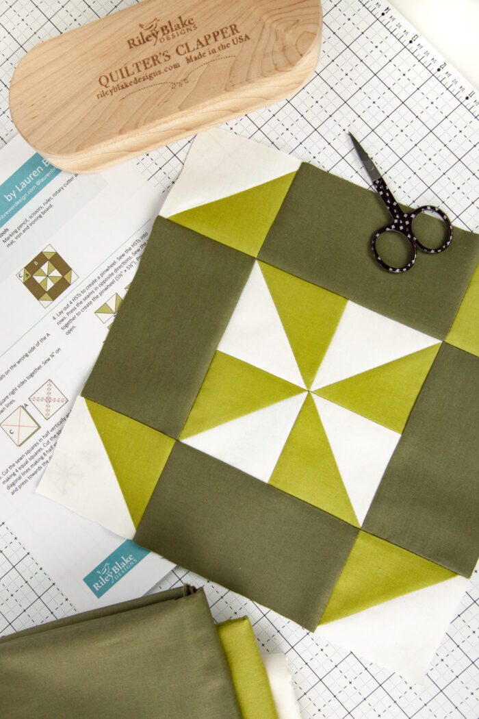 green and white quilt block on white cutting board