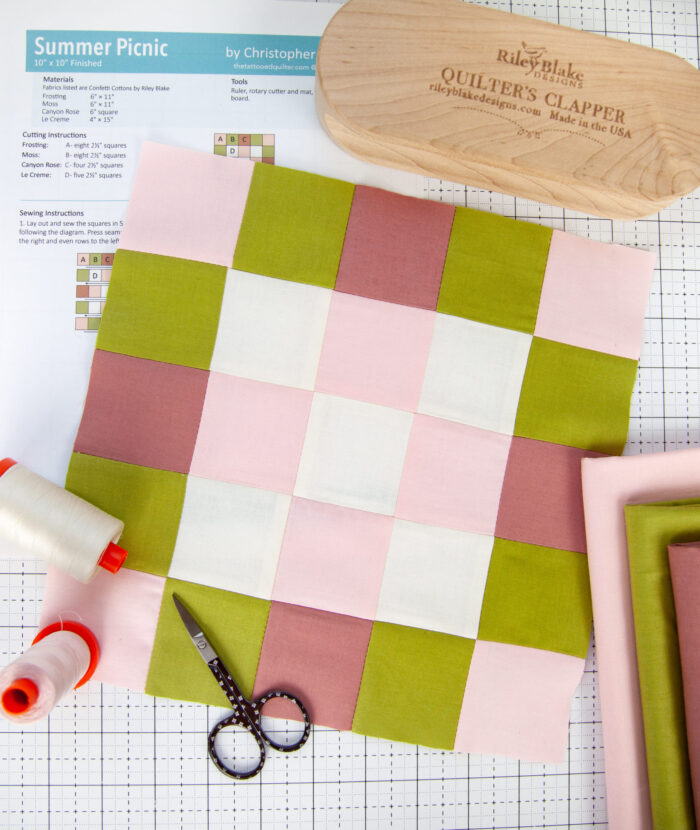pink, olive and white quilt block on white cutting mat