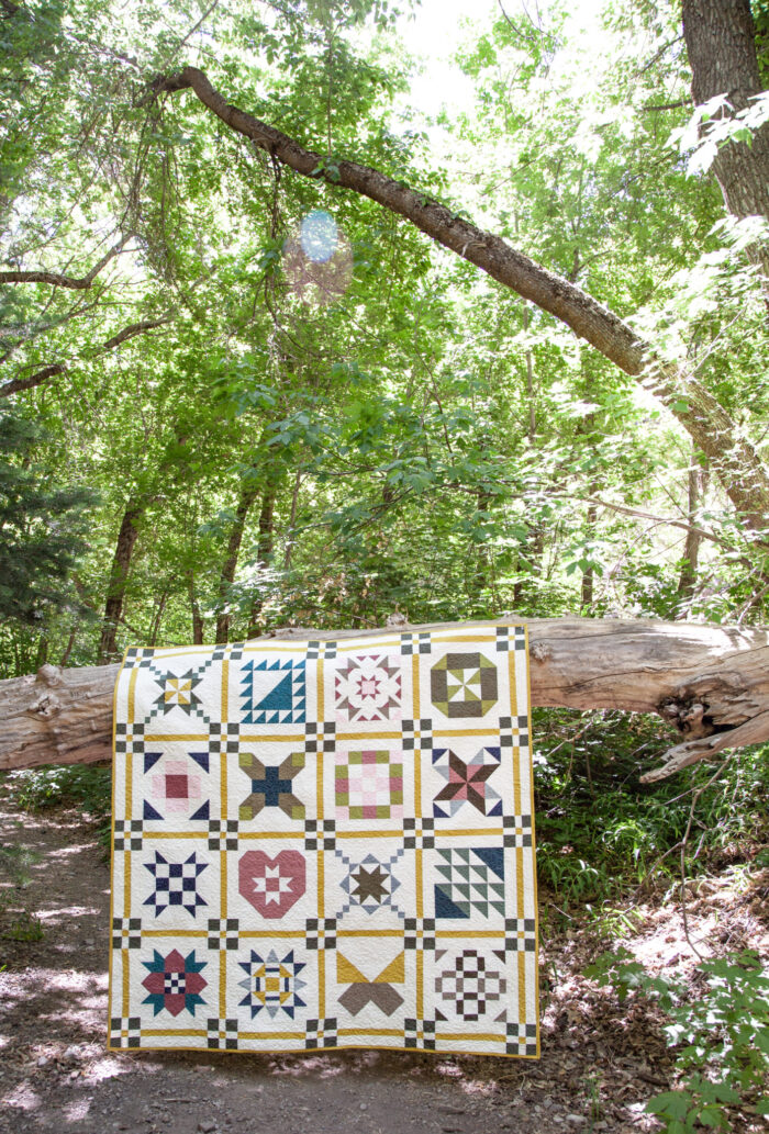 colorful quilt draped over wood log outdoors