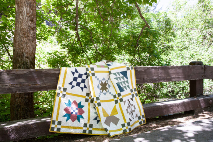 colorful quilt draped over wood fence outdoors