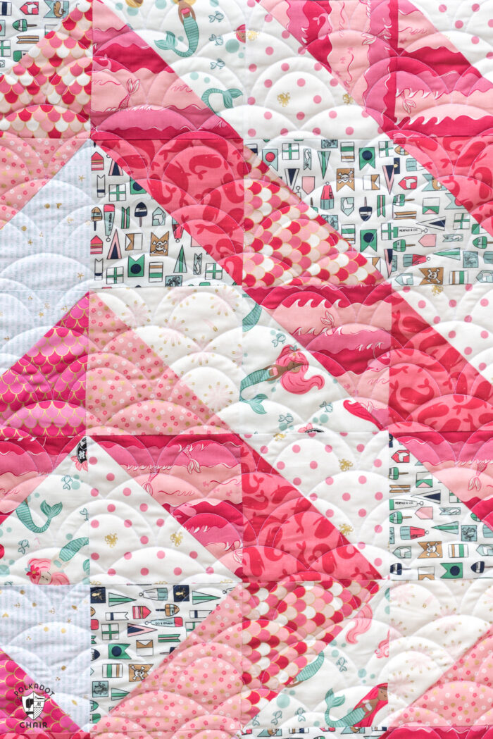 close up of coral and white baby quilt