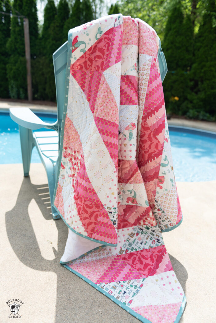 coral and white quilt draped over chair by pool