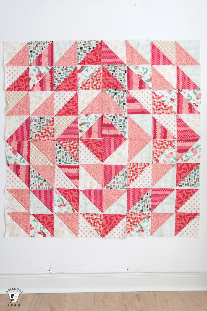 diagram of coral and white half square triangle quilt blocks arranged into 8 rows of 8 squares
