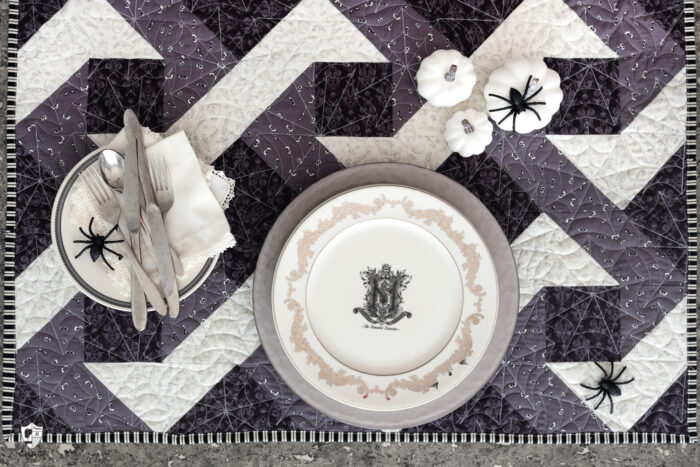 Halloween table setting with gray and black quilted table topper and white plates