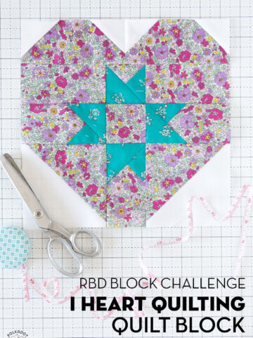 pink floral and turquoise quilt block on white cutting mat