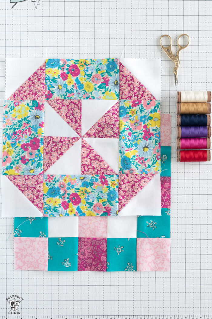 pink, blue, aqua and white quilt block and colorful thread on white cutting mat